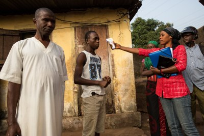 A team of contact tracers visits a community in Conakry, Guinea, on January 14, 2015 after a family member was infected with Ebola. A community workers, followed by a team of doctors, measures the temperature of a family member.