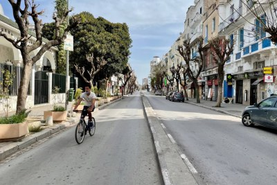 A young man cycles down an empty street in Tunis.