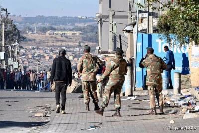 Des membres des Forces de défense sud-africaines au sol à Alexandra le 13 juillet 2021.