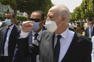 Le président tunisien Kaïs Saïed levait son poing en marchant sur l'avenue Bourguiba à Tunis, entouré de gardes du corps, le 1er août 2021.